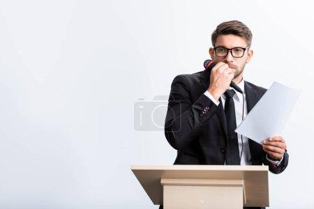 Photo pour Homme d'affaires effrayé en costume debout à la tribune et tenant un microphone pendant la conférence isolé sur blanc - image libre de droit