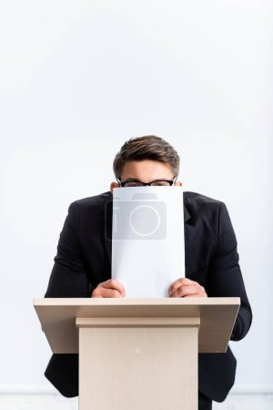 Photo for Scared businessman in suit standing at podium tribune and obscuring face with paper during conference isolated on white - Royalty Free Image