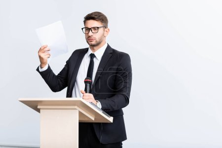 Photo for Scared businessman in suit standing at podium tribune and holding microphone during conference isolated on white - Royalty Free Image
