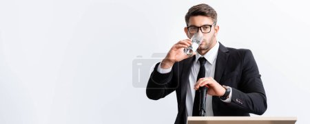 Photo for Panoramic shot of scared businessman in suit standing at podium tribune and drinking water during conference isolated on white - Royalty Free Image