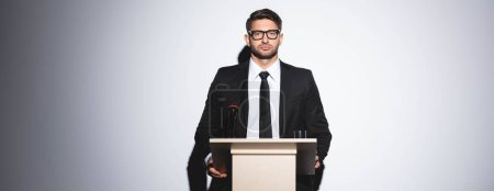 Photo for Panoramic shot of businessman in suit standing at podium tribune and looking at camera during conference on white background - Royalty Free Image