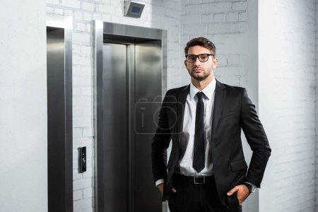 Photo pour Homme d'affaires en costume avec les mains dans les poches debout près de l'ascenseur - image libre de droit