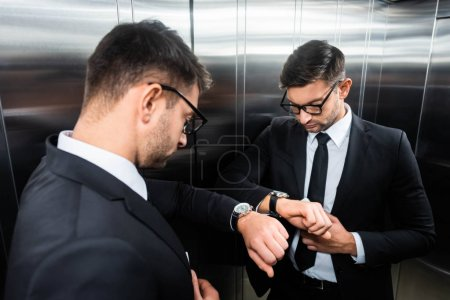Photo pour Bel homme d'affaires en costume regardant montre-bracelet dans l'ascenseur - image libre de droit