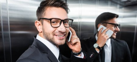 panoramic shot of smiling businessman in suit talking on smartphone in elevator