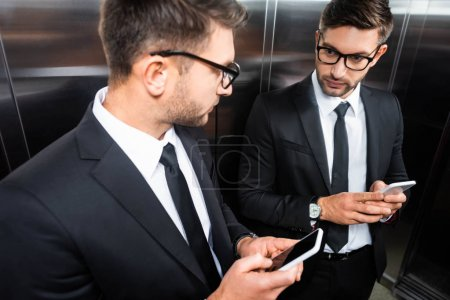 Photo for Selective focus of businessman in suit holding smartphone and looking at mirror in elevator - Royalty Free Image