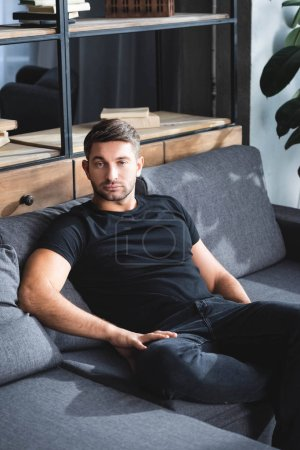 handsome man in black t-shirt sitting on sofa in apartment