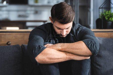 Photo pour Handsome and sad man in shirt hugging legs in apartment - image libre de droit