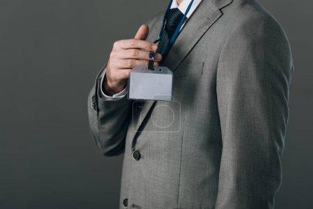 Photo pour Vue en croix de l'homme en costume tenant l'insigne isolée sur gris - image libre de droit