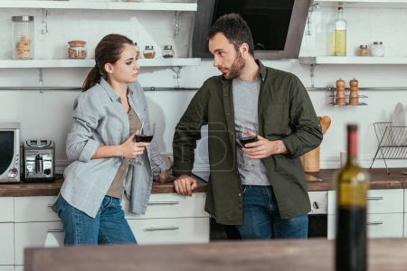 Photo for Selective focus of couple holding glasses of wine on kitchen - Royalty Free Image