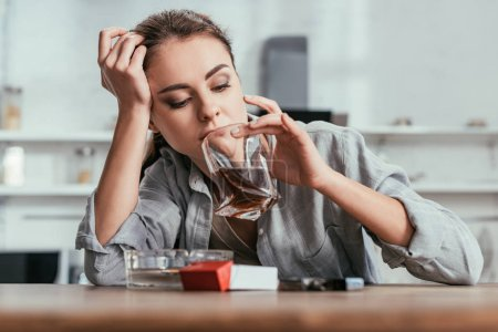 Photo for Woman looking in whiskey glass beside cigarettes on table - Royalty Free Image