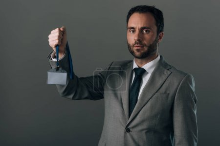 Man in suit holding badge with copy space isolated on grey