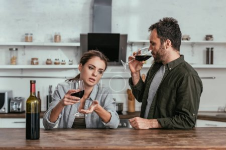 Photo for Alcohol addicted couple drinking wine and talking on kitchen - Royalty Free Image