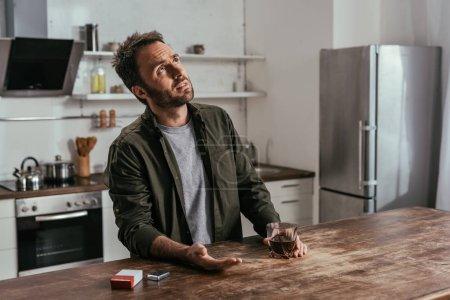 Mann hält Whiskey-Glas in der Hand und blickt auf Küchentisch