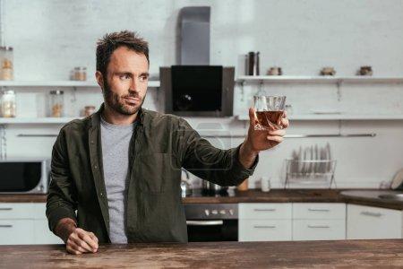 Photo pour Homme avec verre de whisky grillé à quelqu'un sur la cuisine - image libre de droit