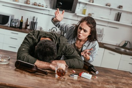 Photo for Angry woman quarreling with drunk husband with alcohol addiction on kitchen - Royalty Free Image