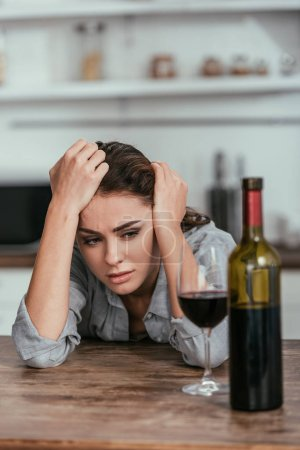 Photo for Selective focus of depressed woman looking at wine on table - Royalty Free Image
