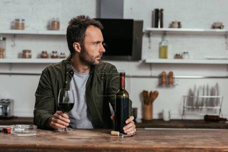Hombre con copa de vino y botella mirando a la mesa de la cocina