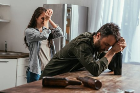 Photo for Selective focus of crying woman with alcohol addicted husband on kitchen - Royalty Free Image