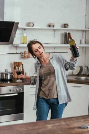 Alkoholabhängige Frau hielt Weinglas und Flasche in Küche