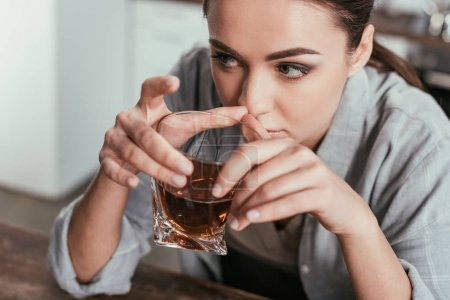 Photo for High angle view of woman holding whiskey glass and looking away - Royalty Free Image