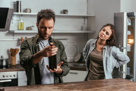 Photo for Selective focus of alcohol depended man with wine bottle and sad wife on kitchen - Royalty Free Image