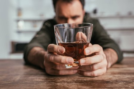 Photo for Selective focus of man holding whiskey glass in hands at table - Royalty Free Image
