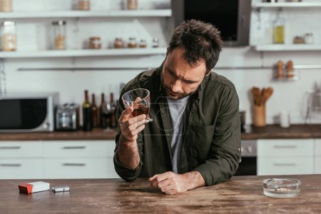 Photo for Worried man with alcohol depended holding whiskey glass at kitchen - Royalty Free Image