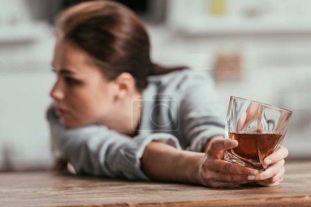 Photo for Selective focus of sad woman holding whiskey glass at table - Royalty Free Image