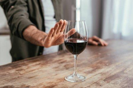 Foto de Vista recortada del hombre tirando de la mano a la copa de vino en la mesa - Imagen libre de derechos