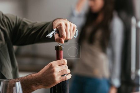 Photo for Selective focus of man opening wine bottle and worried wife at background - Royalty Free Image