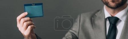 Photo pour Vue en croix de l'homme en costume tenant l'insigne isolée sur fond gris, photo panoramique - image libre de droit