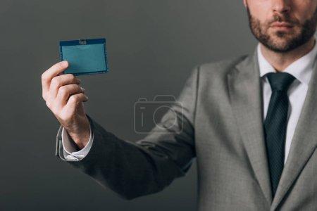 Photo pour Vue recadrée de l'homme en costume tenant insigne avec espace de copie sur fond gris - image libre de droit