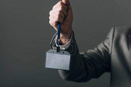Photo pour Vue croustillante d'un homme tenant un insigne isolée sur fond gris - image libre de droit