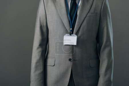 Cropped view of man in suit with badge isolated on grey