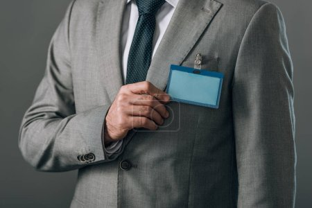 Photo pour Vue recadrée de l'homme avec badge sur costume isolé sur gris - image libre de droit