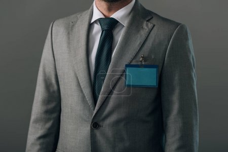 Photo pour Vue en croix de l'homme en costume avec l'insigne isolé sur gris - image libre de droit