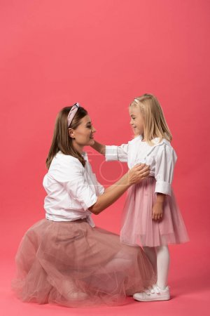 Photo for Side view of smiling daughter and mother hugging on pink background - Royalty Free Image
