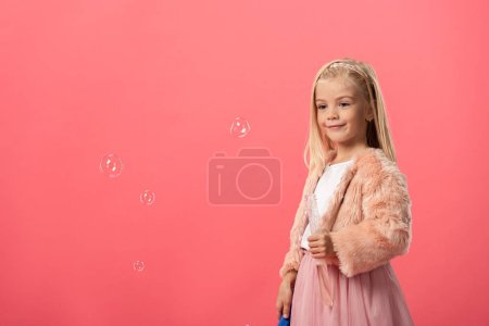 Photo for Cute and smiling kid holding bottle with soap bubbles isolated on pink - Royalty Free Image