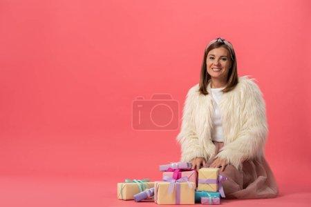 Foto de Atractiva y sonriente mujer sentada cerca de regalos sobre fondo rosa - Imagen libre de derechos