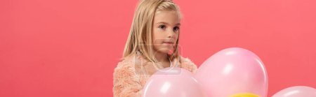 Photo for Panoramic shot of cute and stylish kid holding balloons isolated on pink - Royalty Free Image
