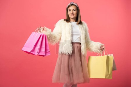 Photo for Attractive and smiling woman holding shopping bags isolated on pink - Royalty Free Image
