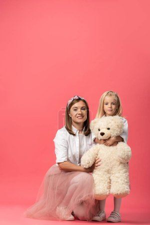 Photo for Daughter with teddy bear and smiling mother looking at camera on pink background - Royalty Free Image