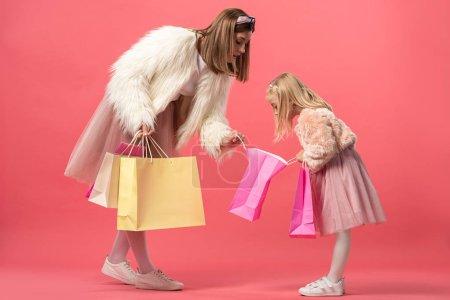 Photo pour Choqué fille et mère regardant sac à provisions sur fond rose - image libre de droit