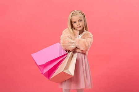 Photo pour Cute kid with crosses arms holding shopping bags isolated on pink - image libre de droit
