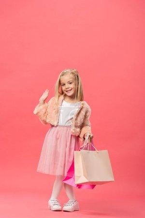 Photo pour Mignon et souriant enfant agitant et tenant des sacs à provisions sur fond rose - image libre de droit