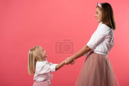 Photo for Side view of smiling daughter and mother holding hands isolated on pink - Royalty Free Image