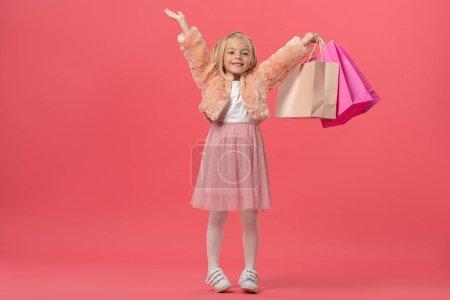Photo pour Mignon et souriant enfant avec les mains tendues tenant des sacs à provisions sur fond rose - image libre de droit