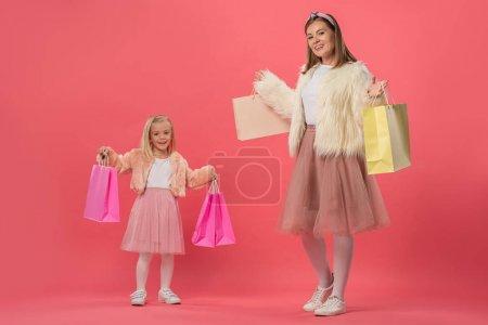 Photo for Smiling daughter and mother holding shopping bags on pink background - Royalty Free Image