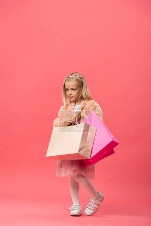 Photo pour Mignon et élégant enfant tenant des sacs à provisions sur fond rose - image libre de droit
