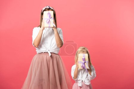 Photo for Daughter and mother obscuring faces with gifts isolated on pink - Royalty Free Image